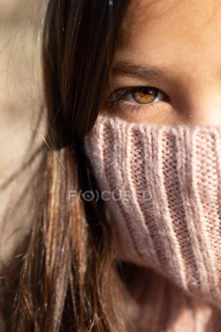 Крупним планом дівчина приховує обличчя в водолазці трикотажного светри і дивлячись на камеру, стоячи на розмитому тлі пляжу — стокове фото