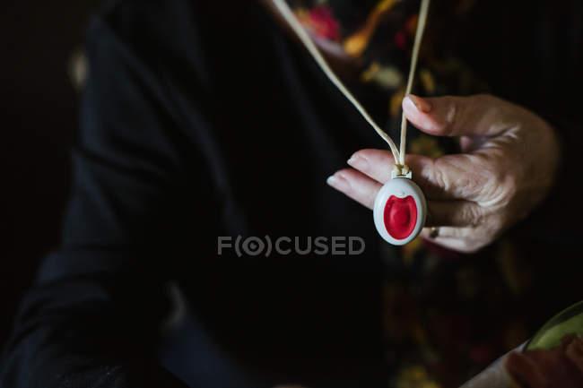 Обрезанное изображение женщины с морщинистой рукой, демонстрирующей кулон с аварийной кнопкой на камеру — стоковое фото