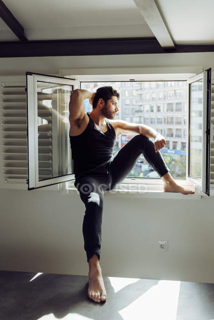 Молодий веселий успішний чоловік у випадковому синглеті сидить на вікні біля ліжка з книжками і озирається геть — стокове фото