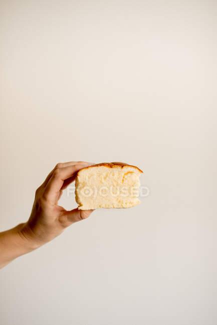 Рука тримає скибочку смачного солодкого бананового торта на коричневому тлі. — стокове фото