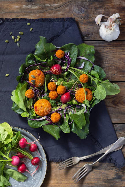 Tasty soy balls and fresh radish placed of green beetroot leaves near napkin and forks on lumber tabletop — Stock Photo