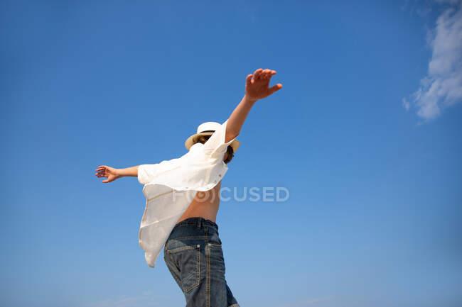De acima mencionado menino atraente em chapéu e camisa desabotoada de pé com as mãos abertas — Fotografia de Stock