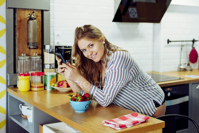 Jovem mulher navegando smartphone na cozinha — Fotografia de Stock