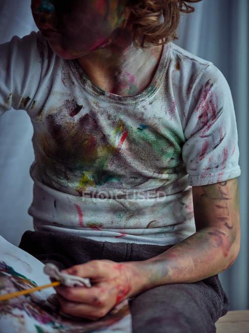 Творчий хлопець у повсякденному одязі, намазаний барвистими фарбами, сидить на стільці і тримає пензель і серветку. — стокове фото