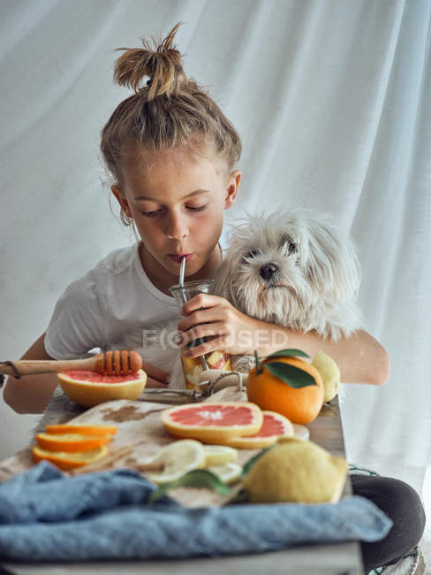 Boy hugging little funny fluffy dog while drinking a lemonade in a glass at table with citrus slices and wooden reamer — Stock Photo