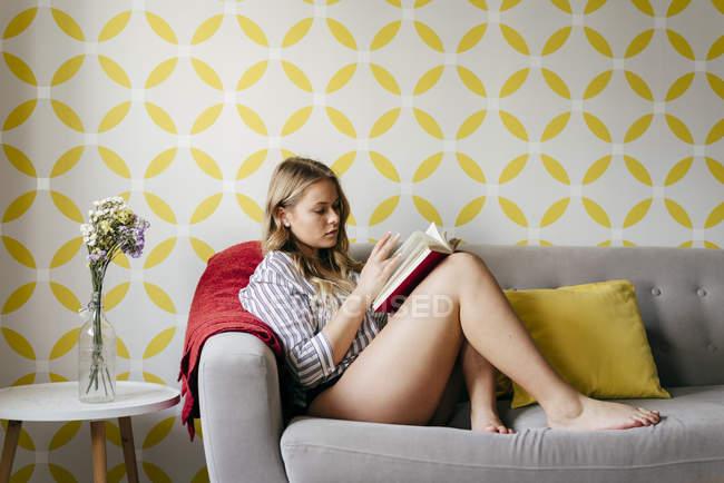 Giovane donna felice lettura libro sul divano — Foto stock