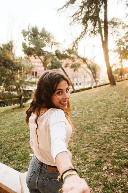 Красивая юная леди улыбается и смотрит в камеру, держа за руку неузнаваемую девушку в парке. — стоковое фото
