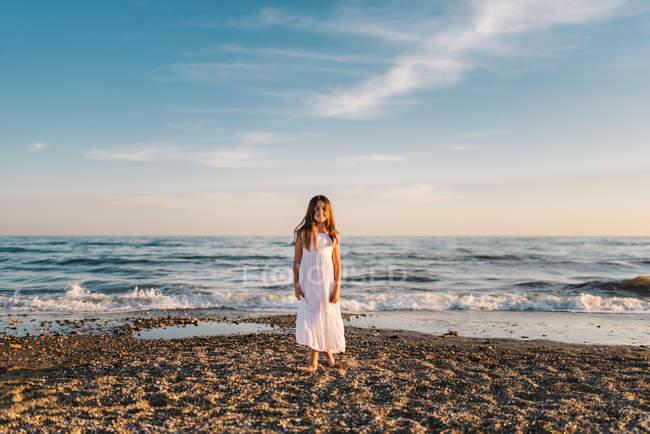 Портрет очаровательной маленькой девочки в белом платье, позирующей на песчаном пляже — стоковое фото