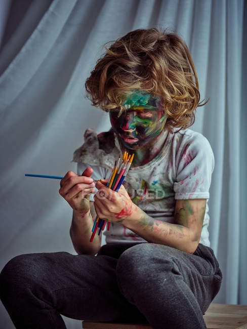 Creative boy in casual clothes smeared in colorful paints holding brushes and sitting on wooden chair — Stock Photo
