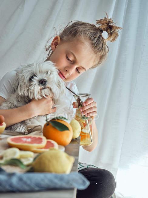 Junge umarmt kleinen lustigen flauschigen Hund, während er versucht, ihm eine Limonade in einem Glas am Tisch mit Zitrusscheiben und hölzerne Reibehalter zu geben — Stockfoto