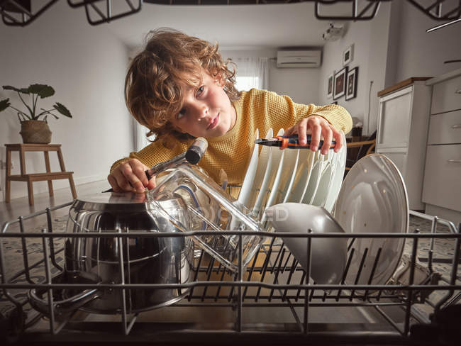 Boy with tools while repairing dishwasher in kitchen — Stock Photo