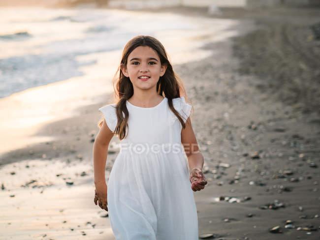Веселий симпатичний жіночий дитина в Білій сукні, що ходить на піщаному березі моря і дивиться на камеру — стокове фото