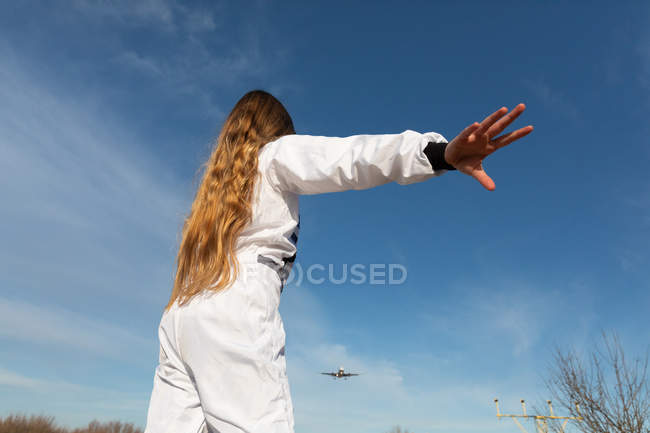 Excited teen girl raising hands against cloudy sky on sunny day — Stock Photo