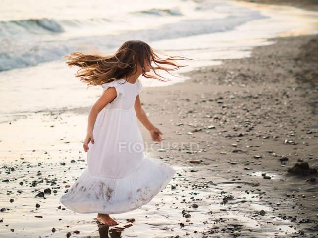 Petite fille en robe blanche jouant au bord de la mer au coucher du soleil — Photo de stock