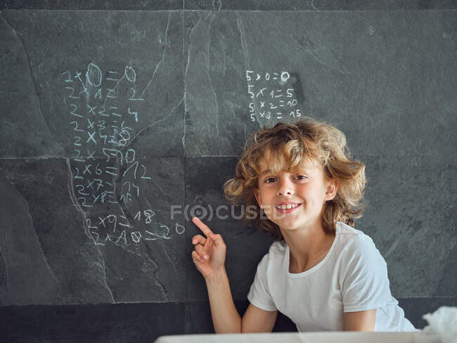 Smiling curly kid showing on multiplication table written by chalk on grey stone wall — Stock Photo