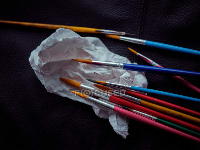 Bright dirty brushes and cute napkin on leather in workshop — Stock Photo