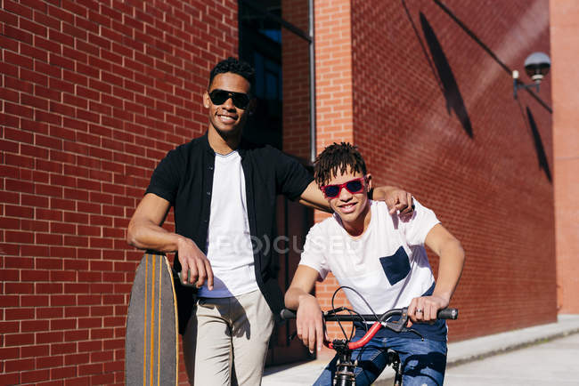 Young happy African American handsome men in casual clothes and sunglasses standing on street with bike and skateboard — Stock Photo