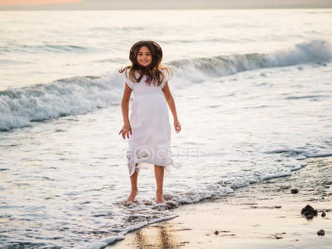 Allegro bambino femminile carino in abito bianco divertirsi sulla spiaggia sabbiosa e guardando la fotocamera — Foto stock
