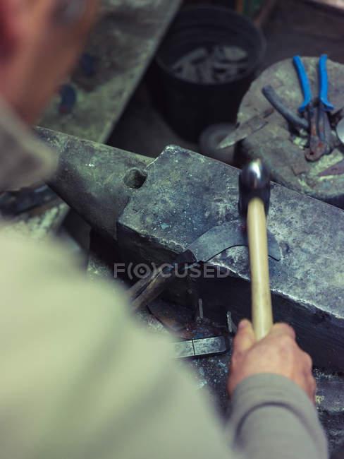 Крупним планом ковальського кування металу з молотком по старій ковадлі в традиційному семінарі — стокове фото