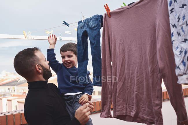 Barbudo hombre adulto sosteniendo sonriente niño mientras colgando ropa mojada en la cuerda en el patio trasero juntos - foto de stock