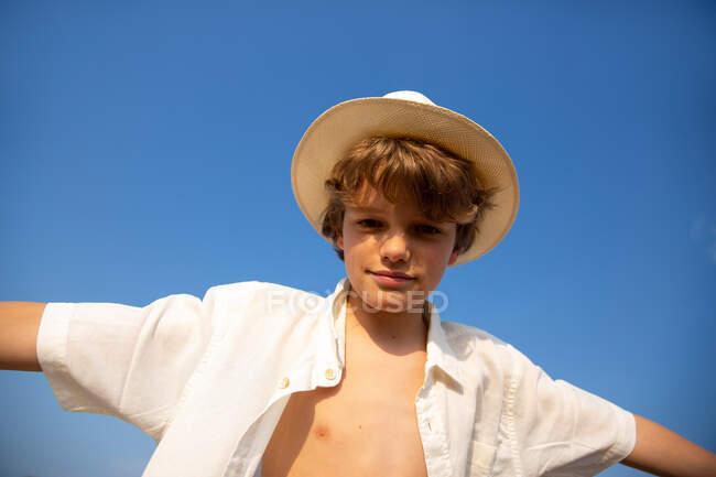 Dall'alto attraente ragazzo in cappello e camicia sbottonata in piedi con le mani aperte — Foto stock
