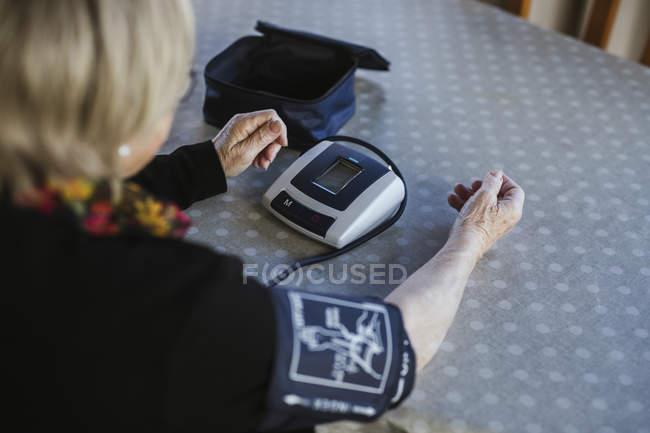 Seniorin misst mit Tensiometer Blutdruck, während sie zu Hause am Tisch sitzt — Stockfoto