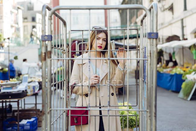 Jeune femme sensuelle en tenue élégante regardant la caméra à travers treillis au marché dans la rue — Photo de stock