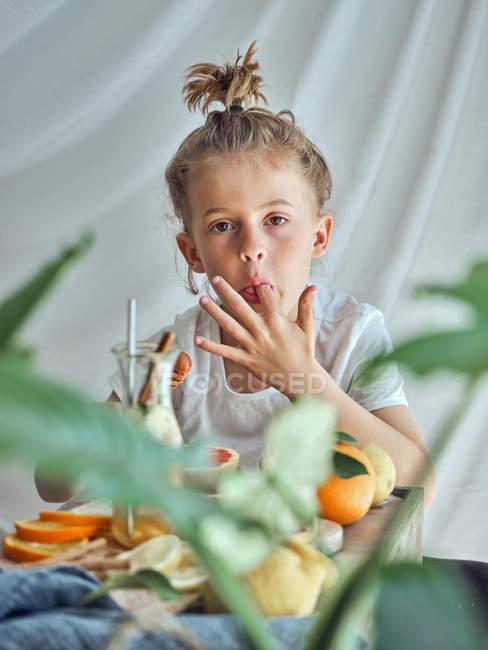 Мальчик в летней одежде со смешной прической готовит грейпфрутовый лимонад — стоковое фото