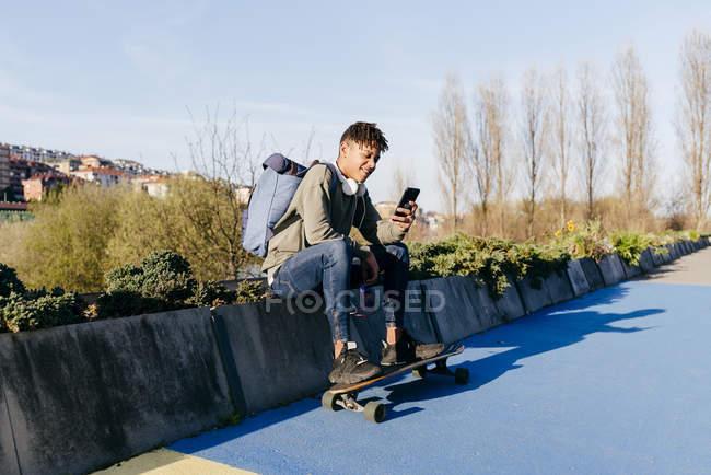 Giovane allegro uomo afroamericano seduto con skateboard — Foto stock