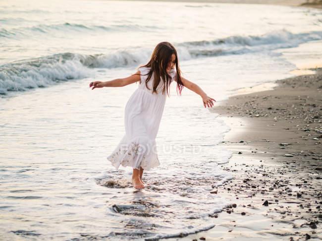 Маленькая девочка в белом платье играет на берегу моря на закате — стоковое фото