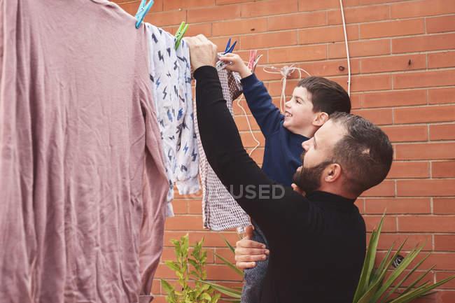 Bärtiger erwachsener Mann hält lächelnden kleinen Jungen, während er nasse Kleidung auf einem Seil im Hinterhof zusammenhängt — Stockfoto