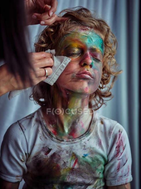 Молода гарненька самиця з серветками прибирає досить творчого хлопця з білявим волоссям, намазаним барвистими фарбами. — стокове фото