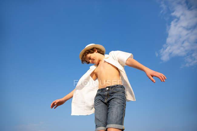 Desde arriba chico atractivo en sombrero y camisa desabotonada de pie con las manos abiertas - foto de stock