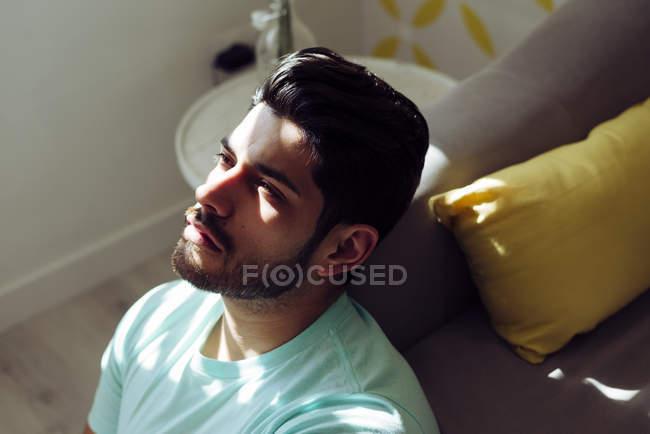 Сверху молодой уставший одинокий мужчина в рубашке, сидящий дома на диване и смотрящий в камеру — стоковое фото