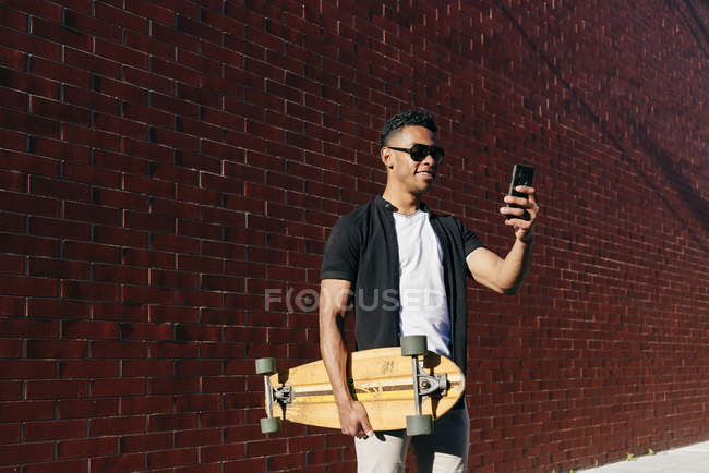 Young black man with long board speaking on phone — Stock Photo
