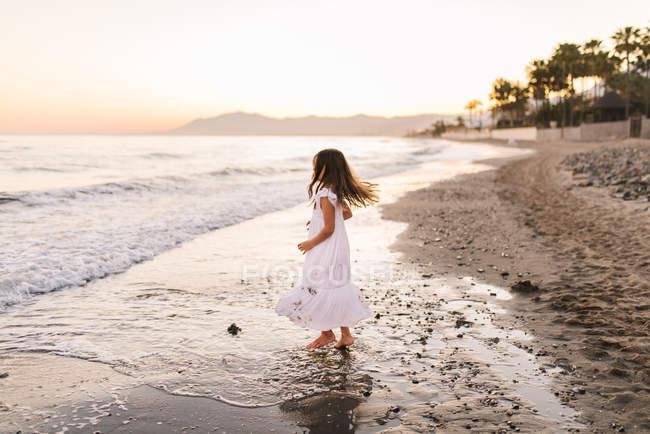 Little girl in white dress walking in water on beach — Stock Photo
