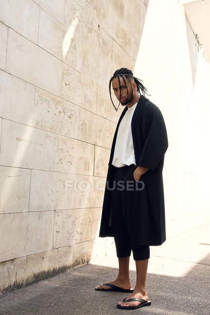 Moda jovem afro-americano masculino em roupa elegante posando na rua perto da parede grungy — Fotografia de Stock