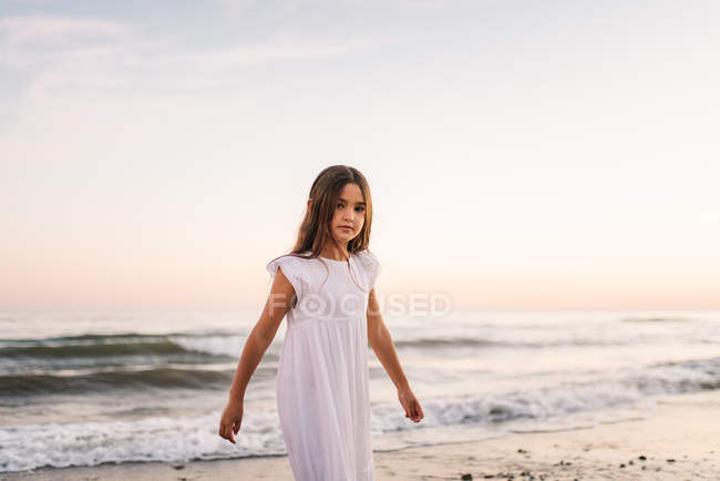 Kleines Mädchen in weißem Kleid, das bei Sonnenuntergang am Strand in die Kamera schaut — Stockfoto