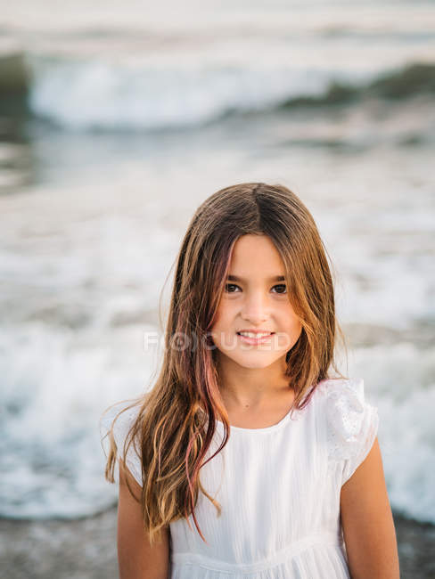 Portrait of charming little girl standing in water on beach and looking at camera — Stock Photo