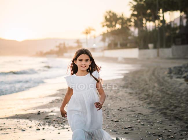 Joyeux enfant féminin mignon en robe blanche marchant sur le bord de mer sablonneux et regardant la caméra — Photo de stock