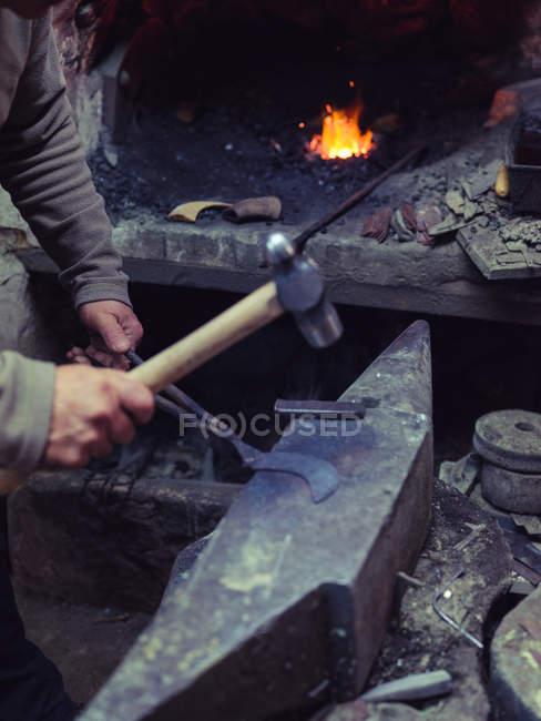 Ковальські руки в рукавичках кування розплавленого металу з молотком по древній ковадлі в традиційному семінарі — стокове фото