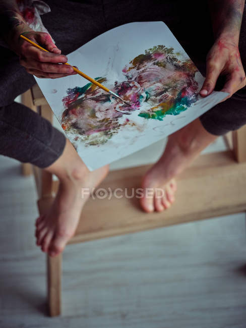 Cropped image of creative boy in casual clothes smeared in colorful paints sitting on chair and holding brush and napkin — Stock Photo