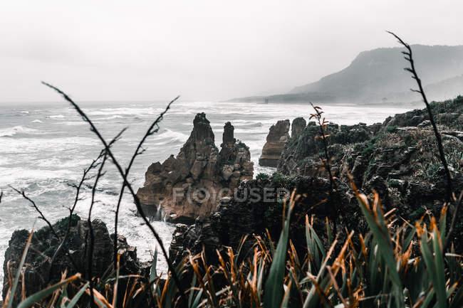 Paisagem do córrego do mar que flui nas rochas no dia nebuloso — Fotografia de Stock