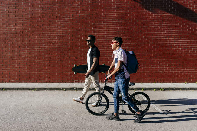 Side view of young black joyful male friends in sunglasses walking in city with bicycle and skateboard — Photo de stock