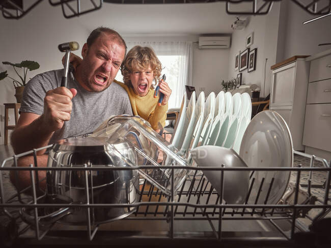 Angry adult man and boy with tools screaming while repairing dishwasher in kitchen — Stock Photo
