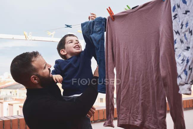 Взрослый мужчина с бородой держит улыбающегося маленького мальчика, вешая мокрую одежду на веревку на заднем дворе вместе — стоковое фото