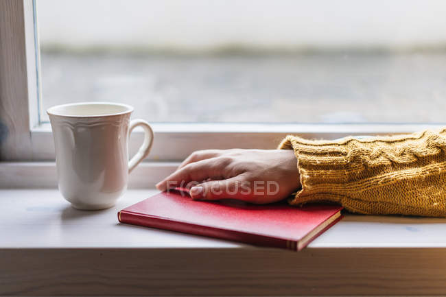 Person hand in yellow cozy warm sweater with book and cup of tea on window sill. — Stock Photo