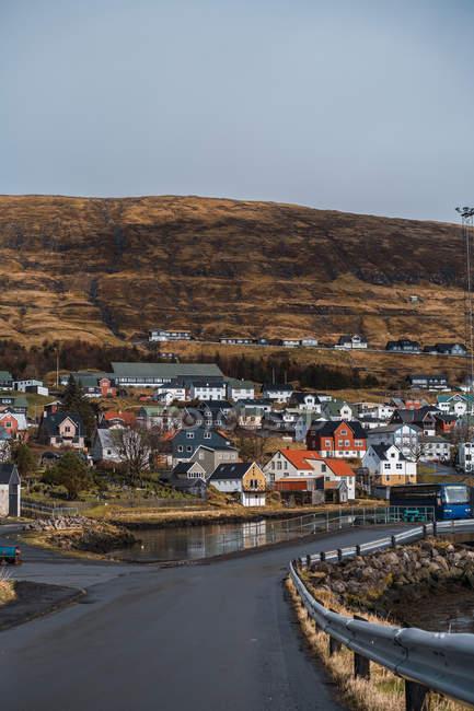 Schöne Häuser einer kleinen Stadt in der Nähe eines kleinen Sees unter einem Hügel am sonnigen Tag auf den Färöern. — Stockfoto