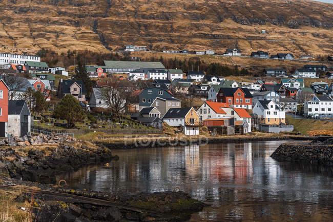 Schöne Häuser einer kleinen Stadt in der Nähe eines kleinen Sees unter einem Hügel am sonnigen Tag auf den Färöern — Stockfoto