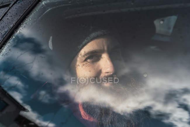 Веселий бородатий чоловік сидить у машині і дивиться в камеру в подорожі.. — стокове фото